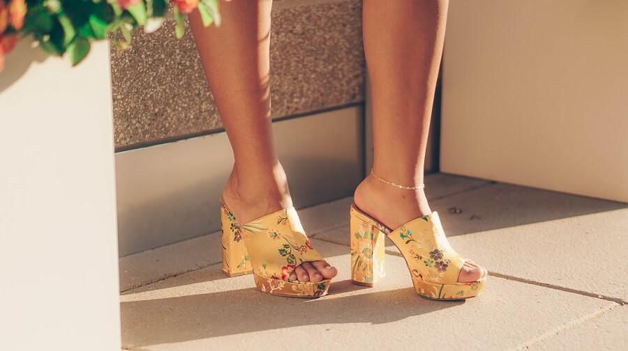 Photo de jambes avec mules jaunes.