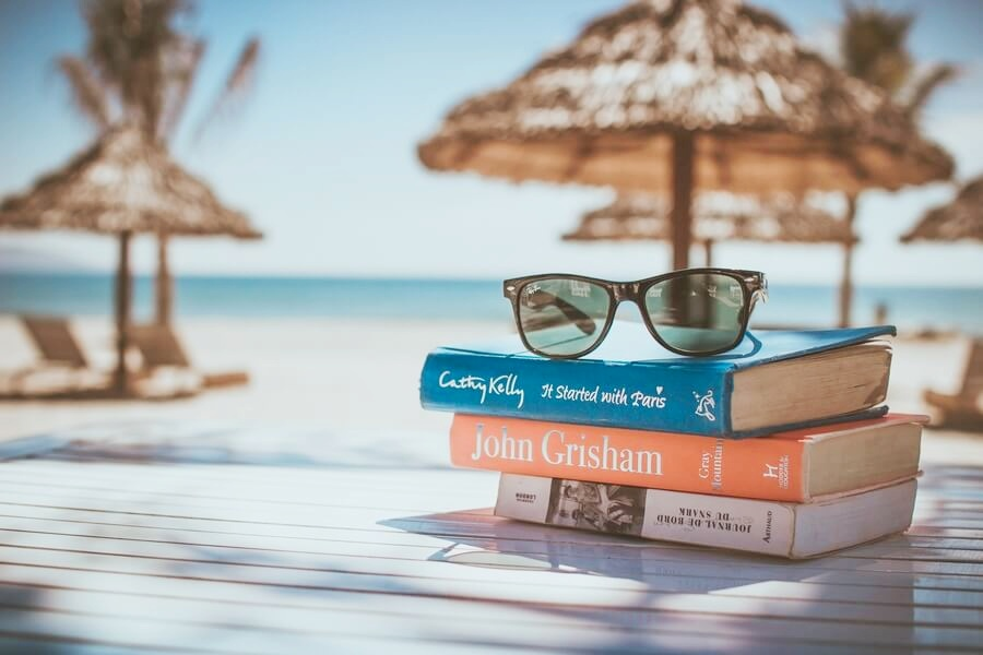 Livres et lunettes de soleil à la plage.